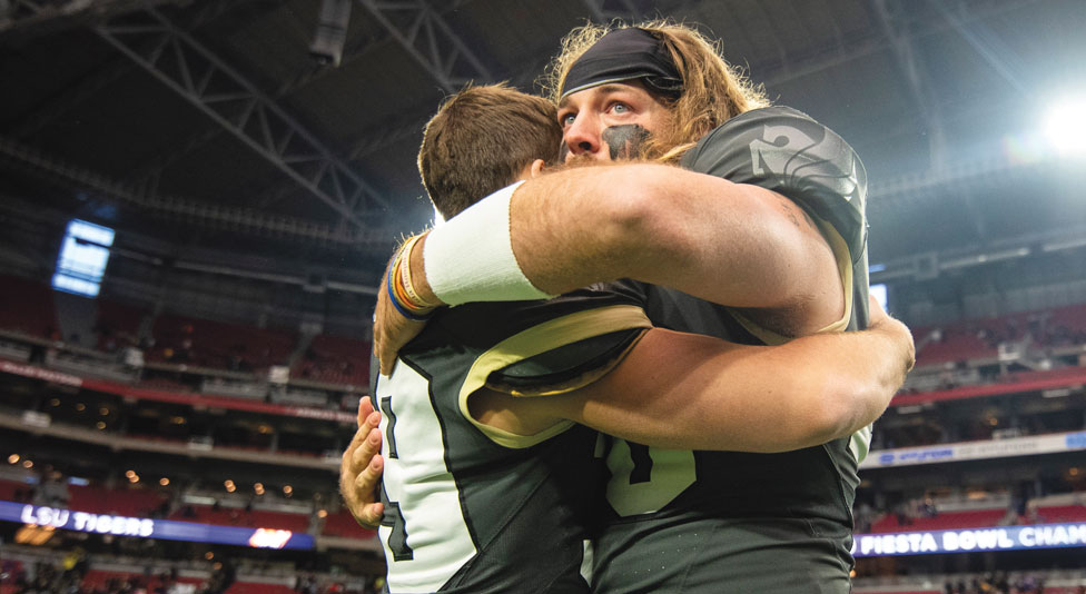 two ucf football players hug after their loss against lsu