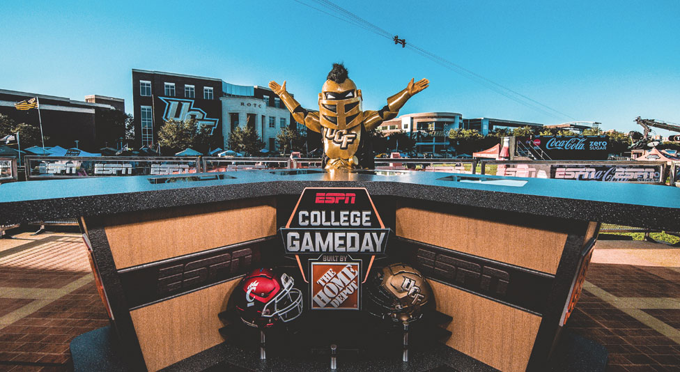ucf mascot knightro standing with arms raised behind the espn college gameday desk