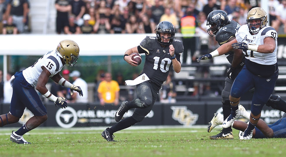 ucf quarterback mckenzie milton runs with the ball away from two navy football players