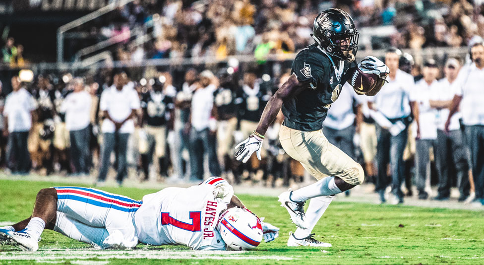 ucf running back Adrian Killins Jr. avoids a tackle from smu football player