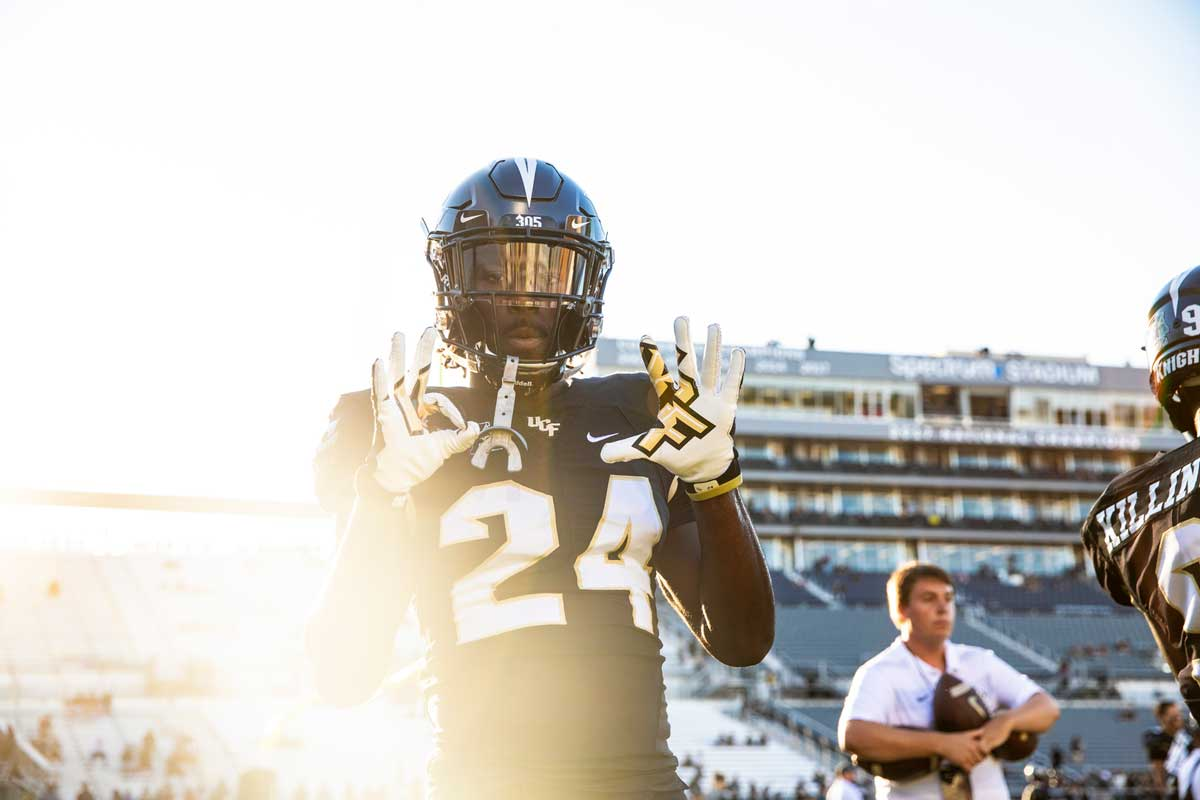 A football player wearing a black #24 jersey pops up his hands, wearing white gloves, with the sun setting in the background.