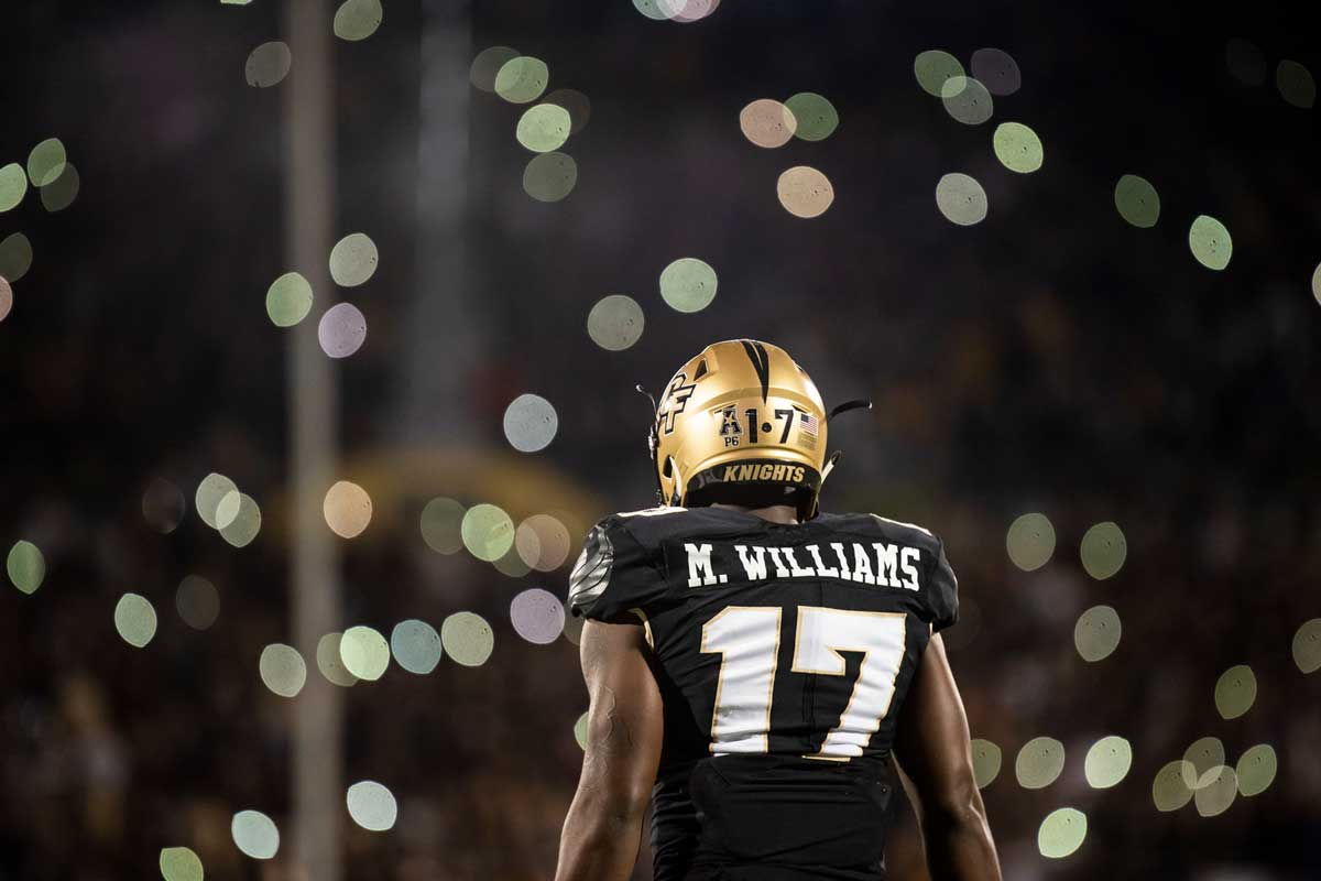 #17 football player looks at gold lights in crowd.