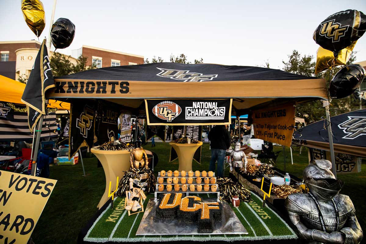 A UCF tailgate tent with balloons, UCF shaped cakes and National Champions banner