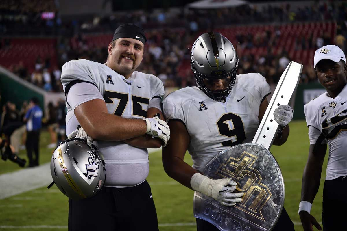 Two UCF football players pose with a silver trophy shaped like an interstate sign on the field