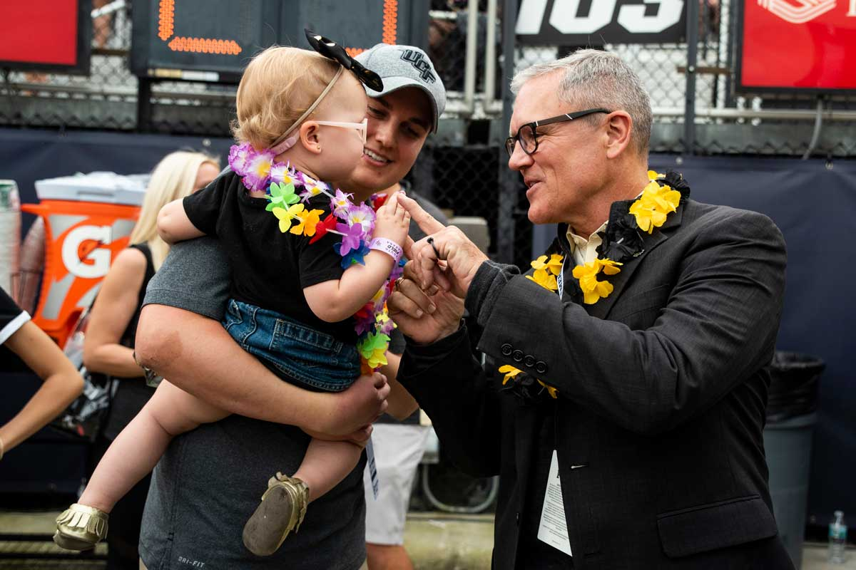 A man with short gray hair wearing black glasses and a black jacket and black and white lei shakes a toddler girl's hand as she is held by her father.