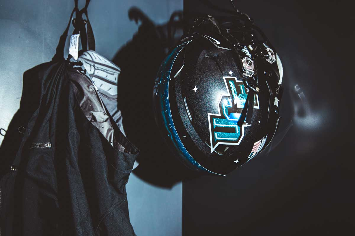 black helmet with blue UCF lettering and a blue stripe down the middle hangs in a locker