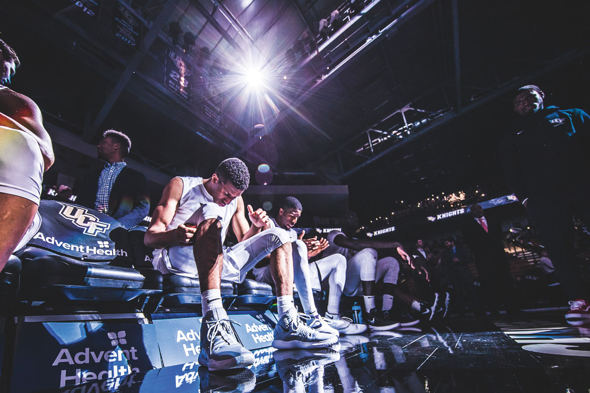 A group of basketball players sit on the sidelines before the start of a game.