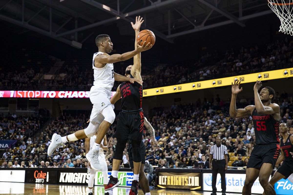 A UCF basketball player jumps to make a shot while a player from the opposing team tries to stop him.
