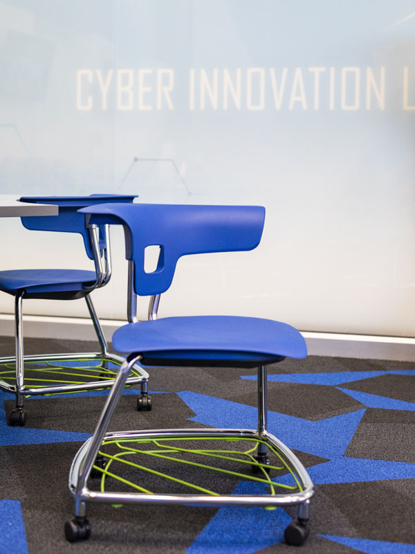 Green baskets sit beneath blue plastic chairs that are on wheels.