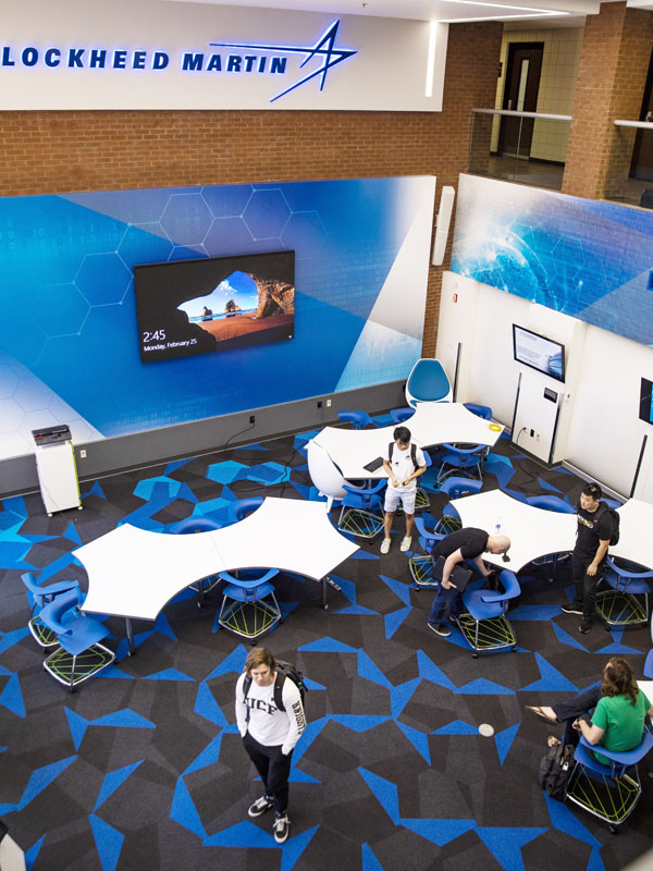 An overhead shot shows a students standing in a room with colorful carpet, whiteboard tables and a TV mounted on the wall.