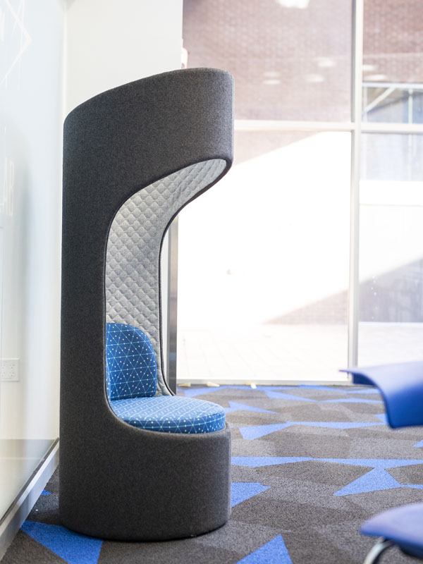 A tall grey chair with a blue seat.