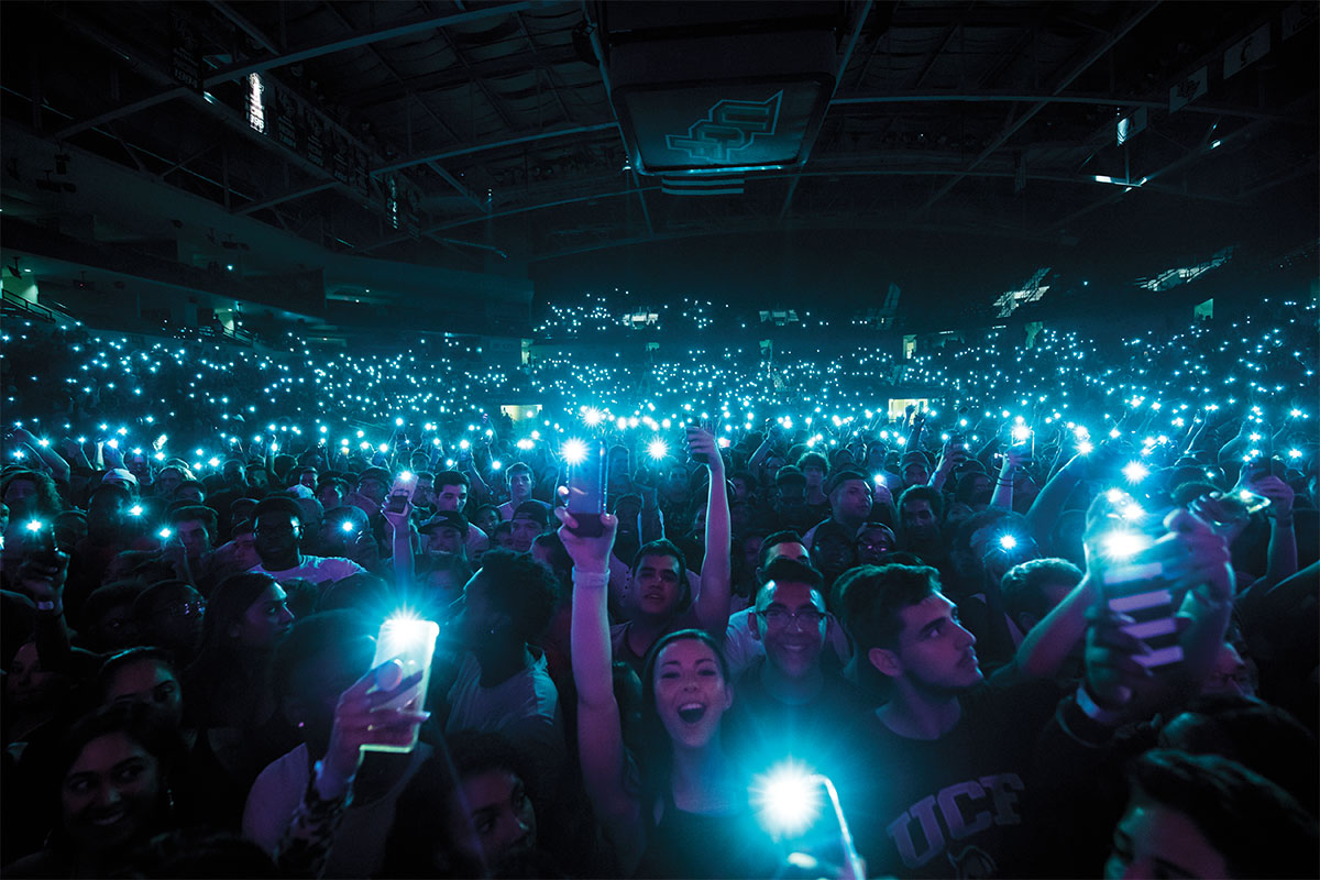 A crowd of students hold up their cellphones with their flashlights on at a concert.