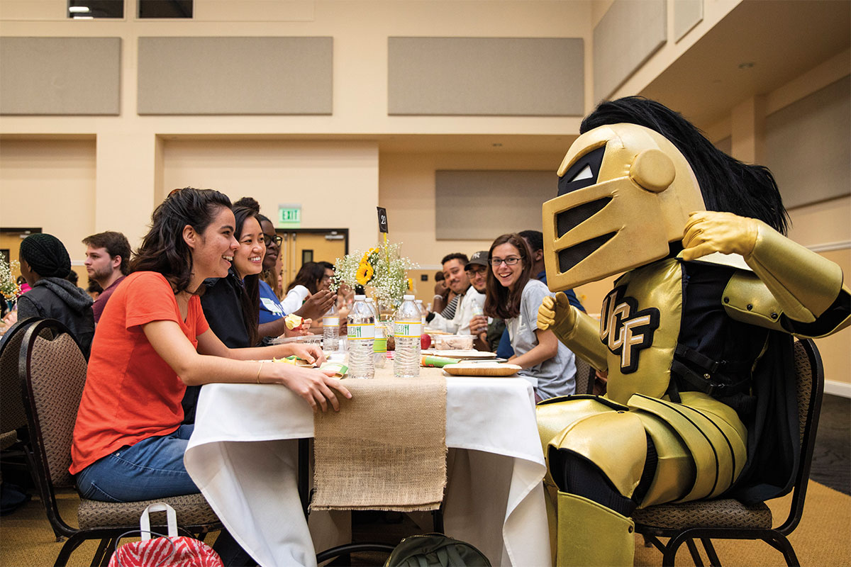 Knightro sits at a banquet table with students.