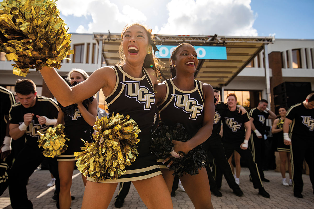 UCF cheerleaders smile while holding black and gold pom-poms outside Millican Hall.