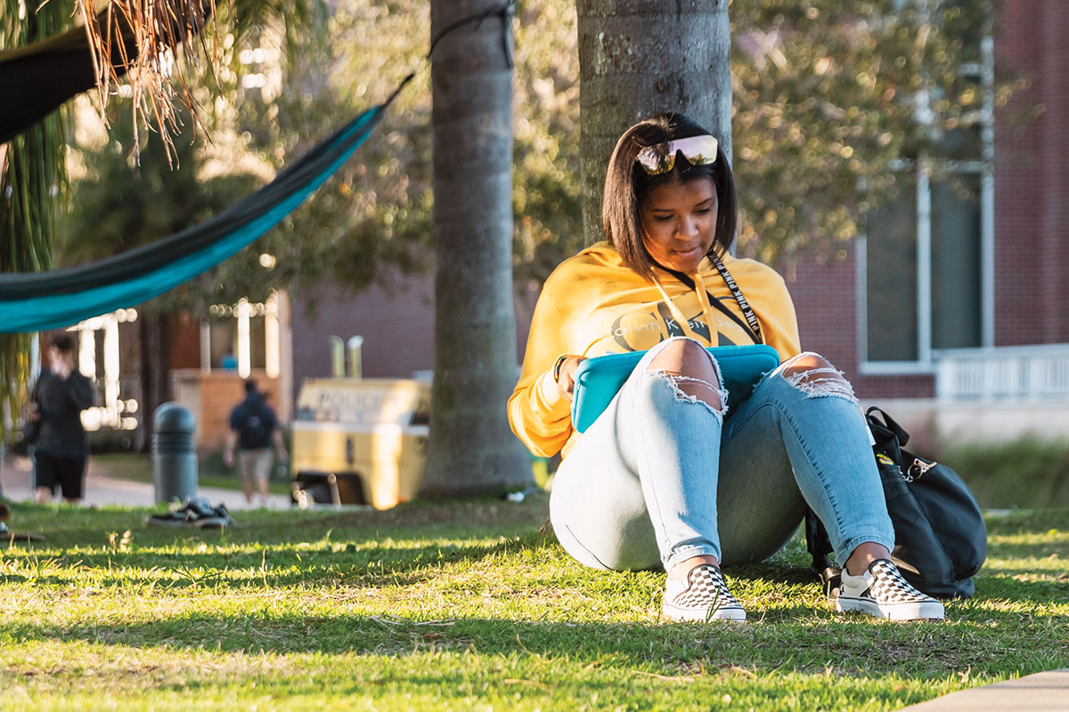A student studies while sitting under a tree with a hammock hanging in the background.