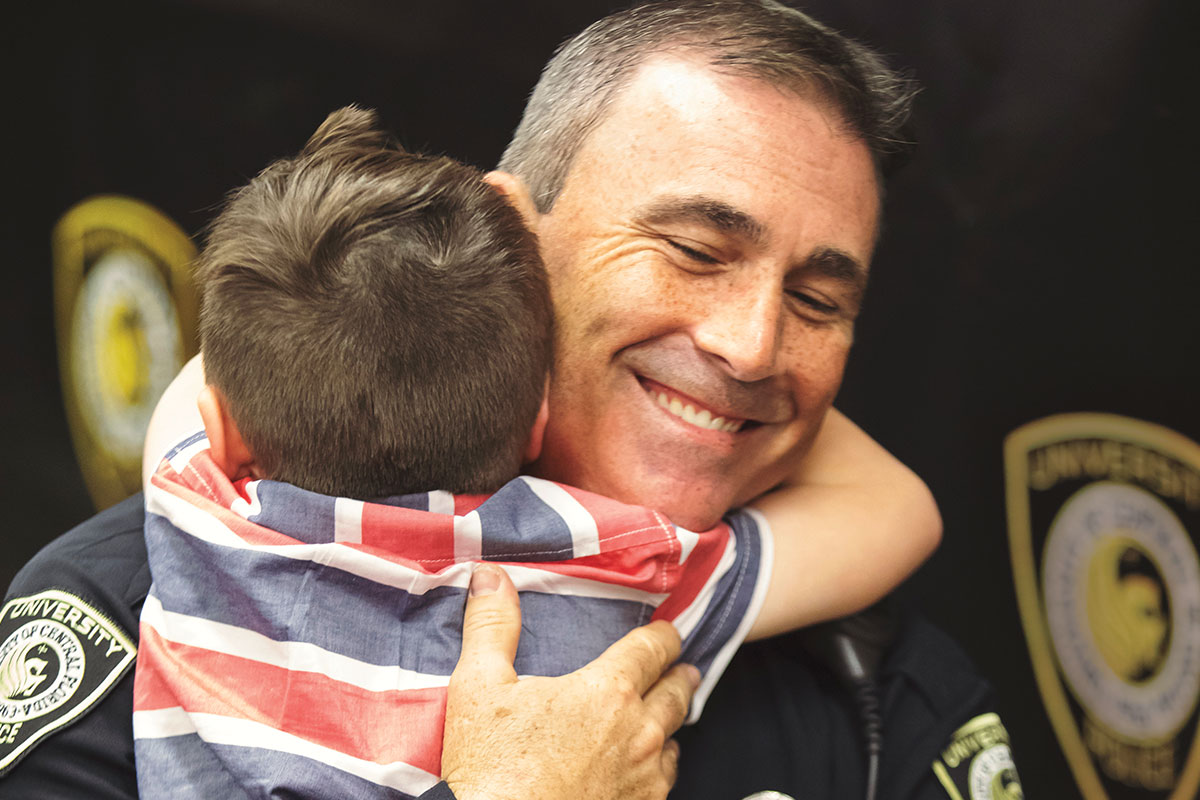 A police officer in uniform hugs a young boy.