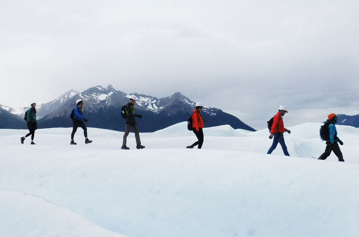 A group of people walking across ice while in front of mountains.