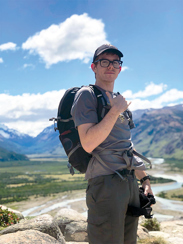 A man with a backpack posing in front of a mountain.