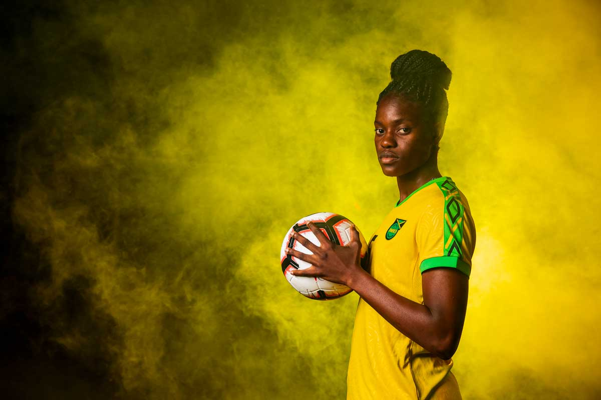 Female soccer player in yellow Jamaica jersey holds soccer ball with yellow smoke behind her