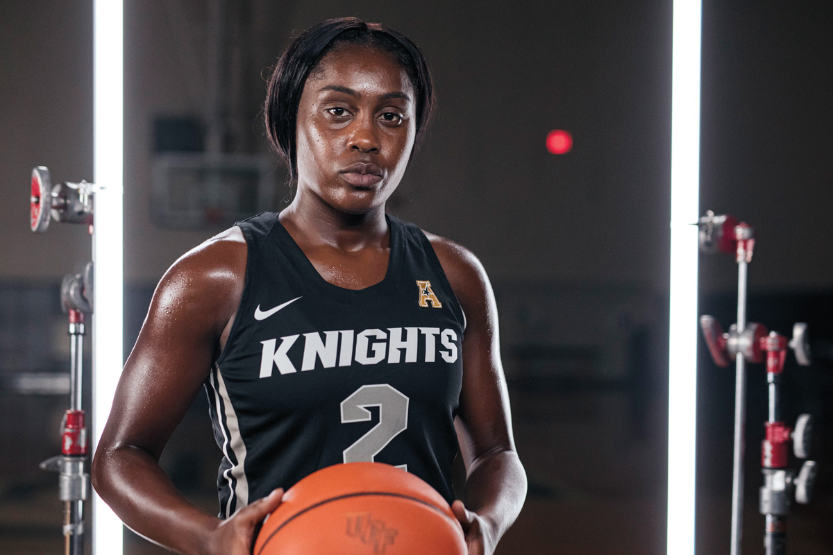 A female basketball player holds a ball while wearing a Knights jersey.