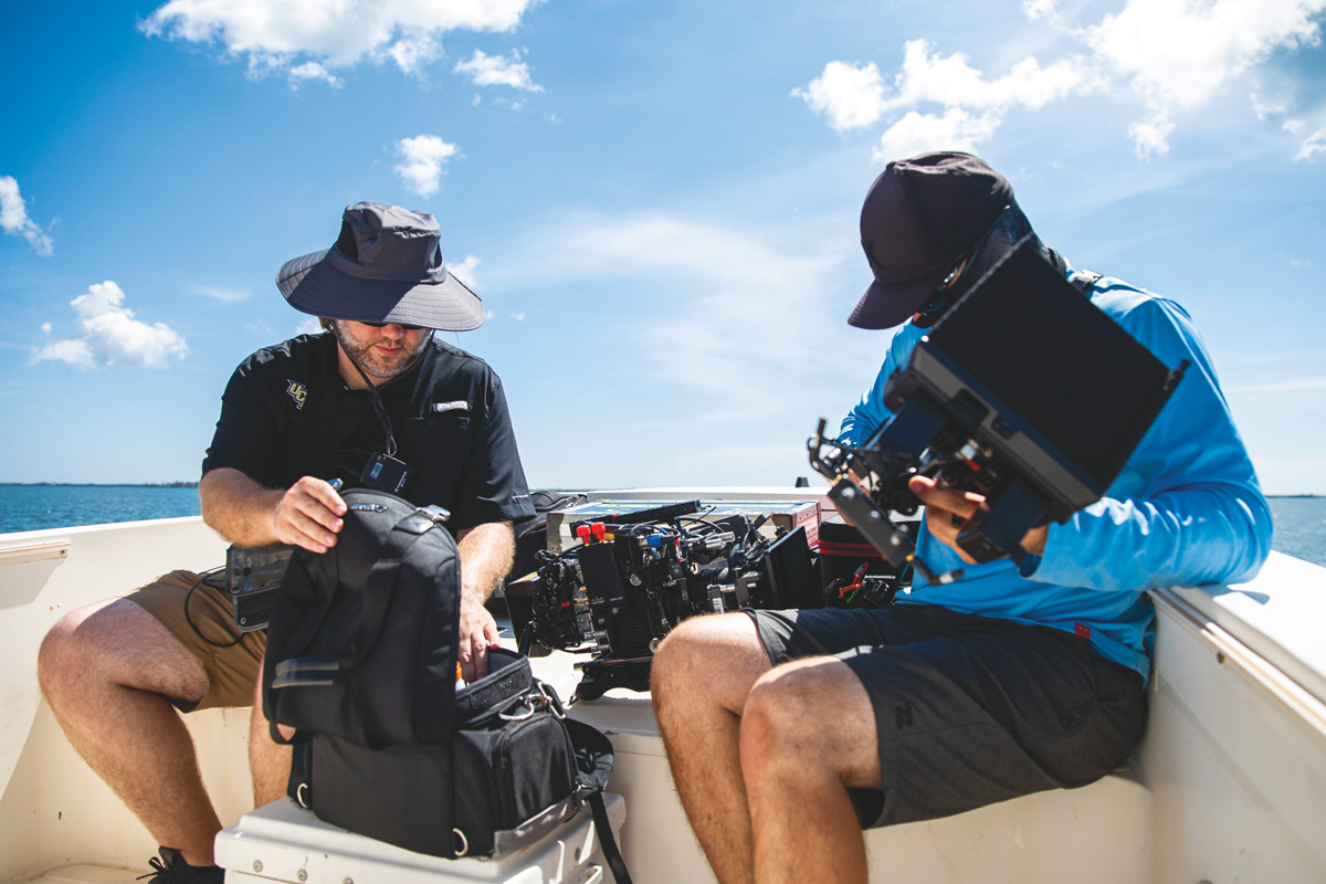 Two cameramen set up their equipment in a boat.