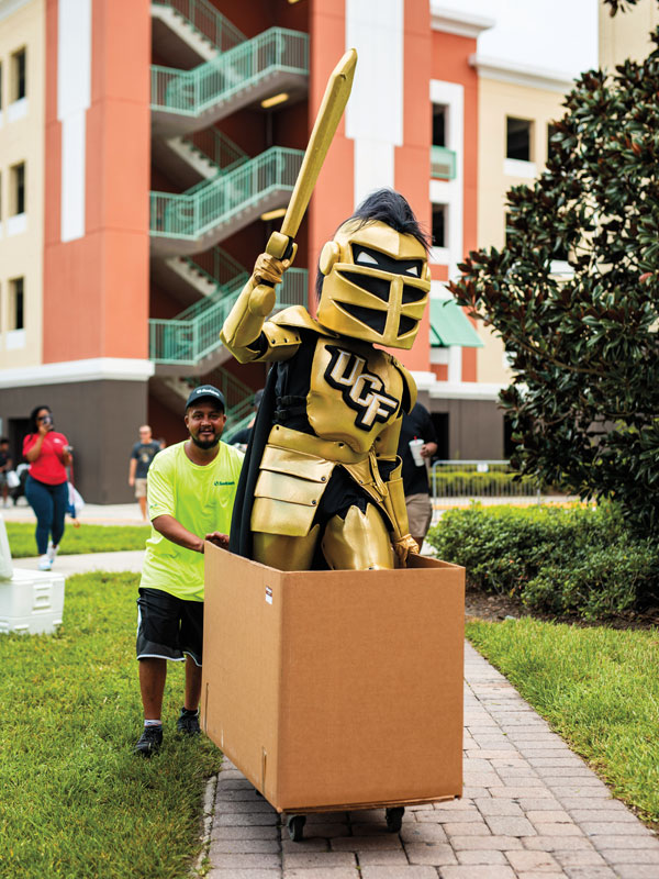 Knightro holds up his sword while standing in a cardboard box being pushed by a mover. UCF Fall 2019