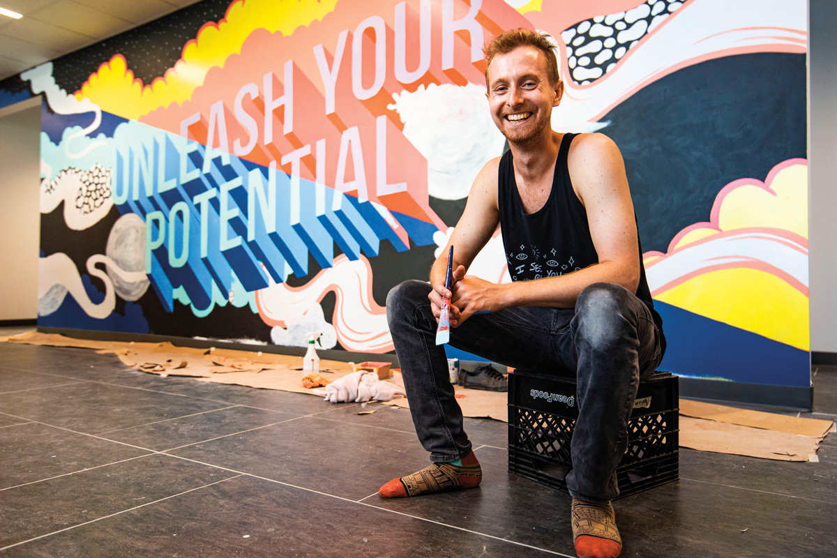 Harry Foreman holds a paint brush in front of a mural that reads