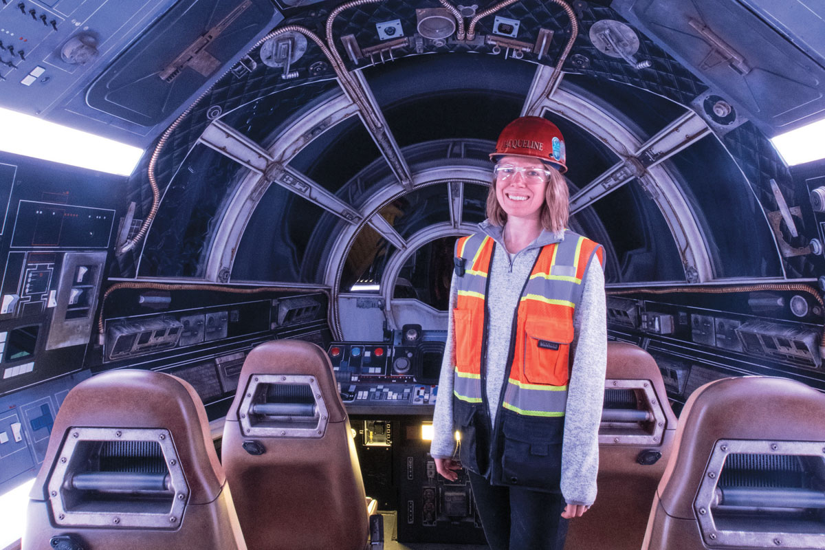 jacqueline king wearing hard hat and reflective vest standing inside millenial falcon