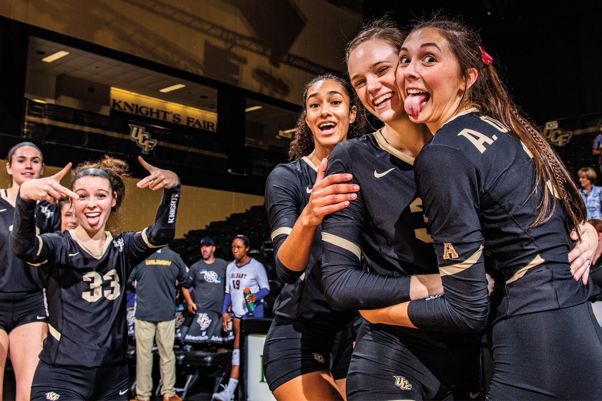 Three volleyball players pose for a photo after a game. UCF Fall 2019