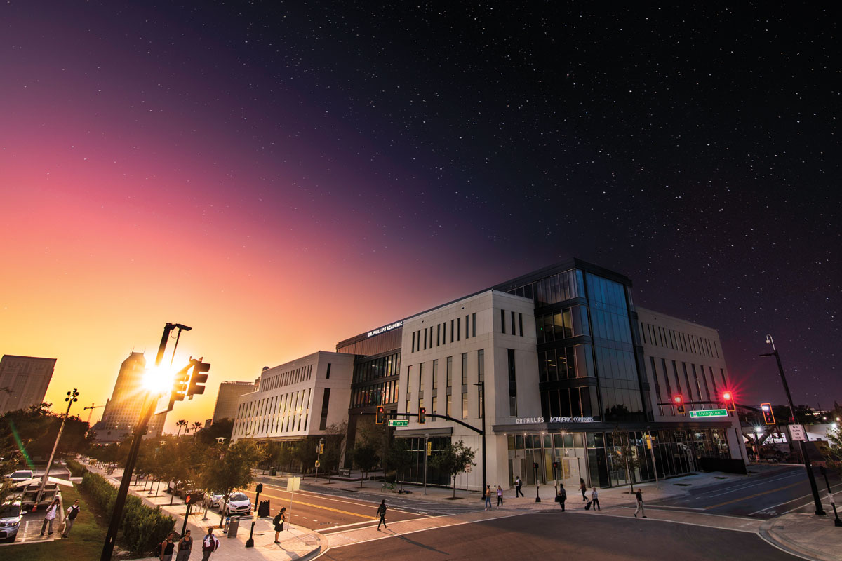 An image of the Dr. Phillips Academic Commons building with the sky behind it changing from day to night.