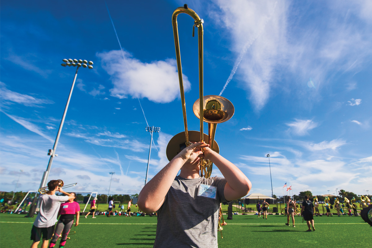 A trombone player plays on a field.