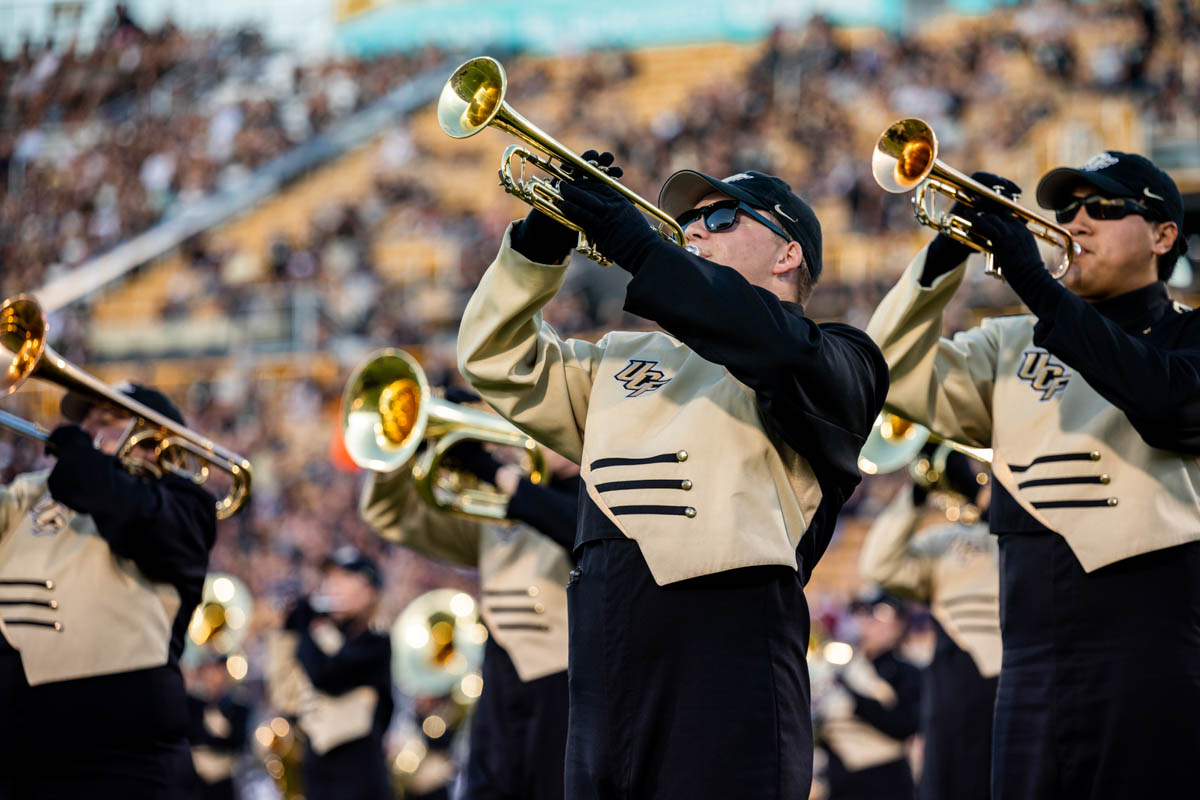 Trumpet players perform on the filed during a football game.