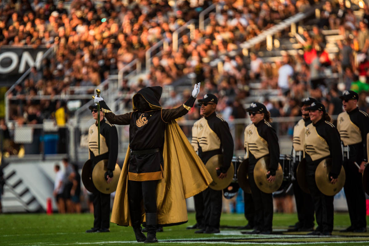 A hooded knight holds a sword while band members holding cymbals stand behind them.