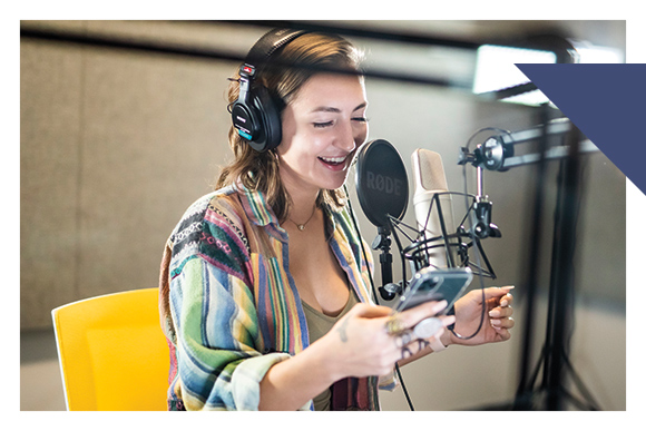Woman in sound booth wears head phones and speaks into microphone