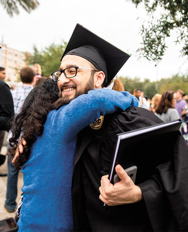Man wearing graduation cap and gown hugs a woman