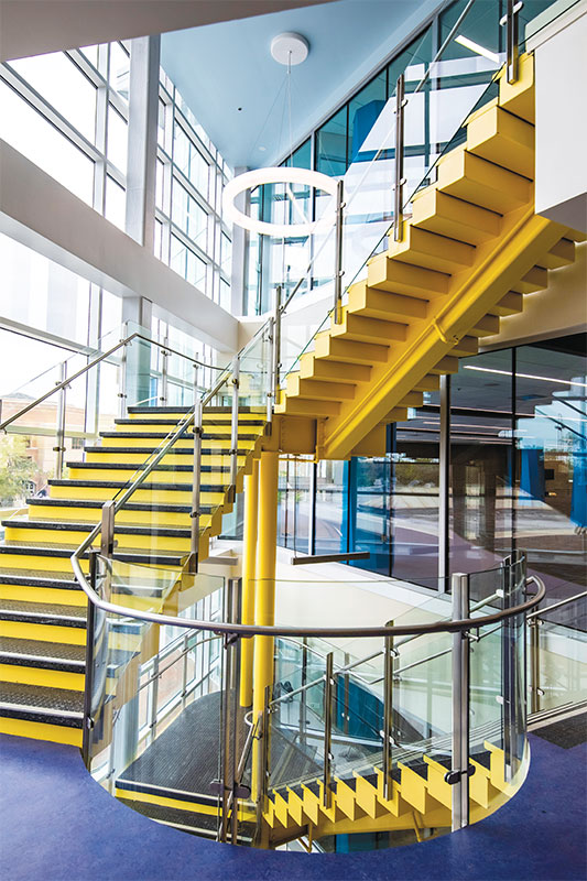 Yellow staircases near large windows.