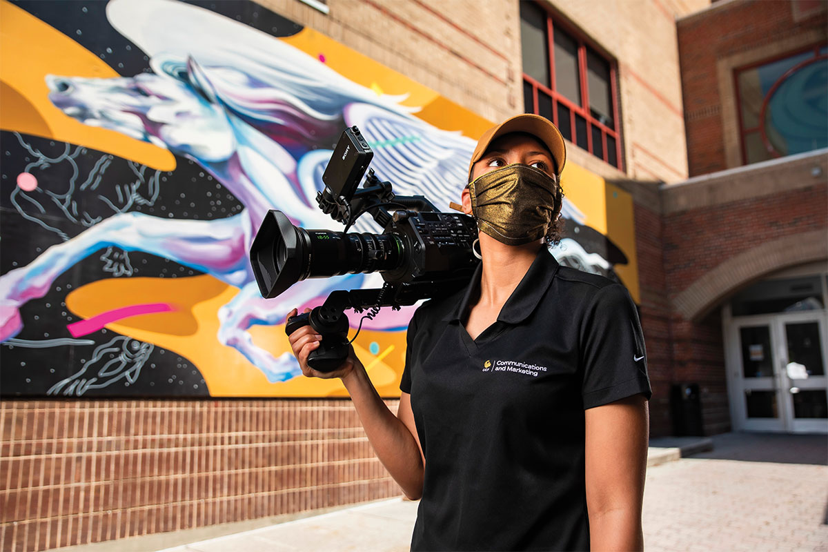 Jasmine Kettenacker wears a mask while holding a camera in front of the Pegasus mural.