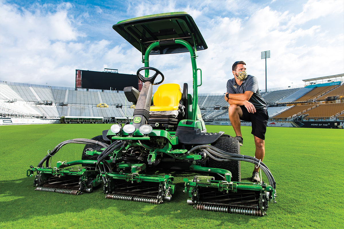 Jon Palmer wears a mask and poses on a piece of landscaping gear while instead Spectrum Stadium.