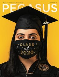 "A graduate wears a cap, gown, necklace that says ""Brave, and a black mask with ""Class of 2020"" in glittery letters."