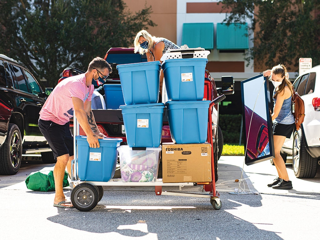 A student and two parents moving items into a dorm