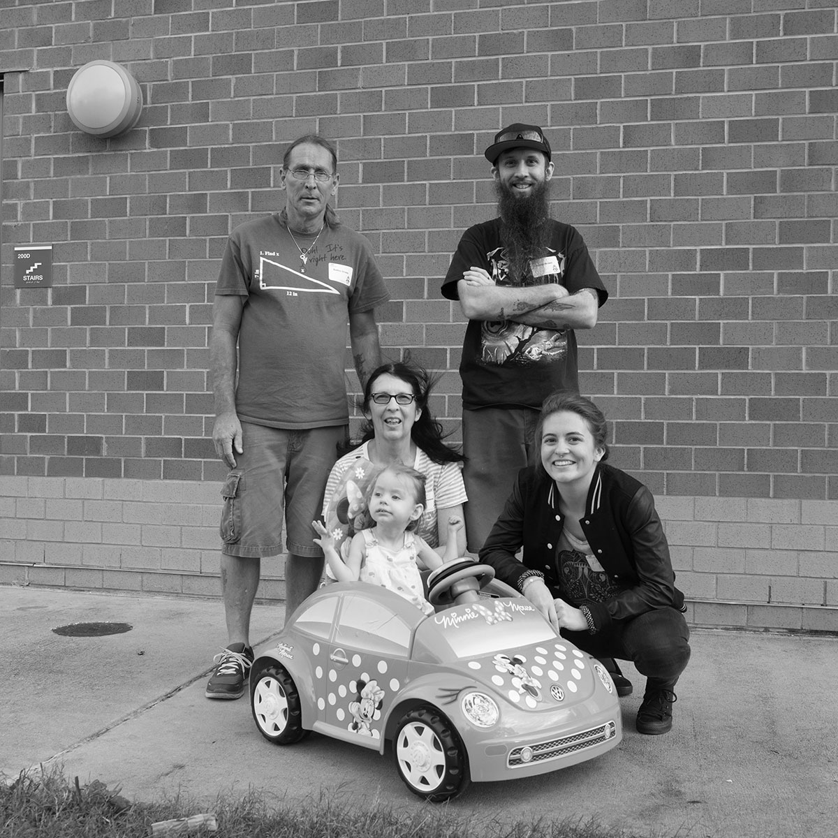 Ava Brown in a Go Baby Go! card with her family posed around her