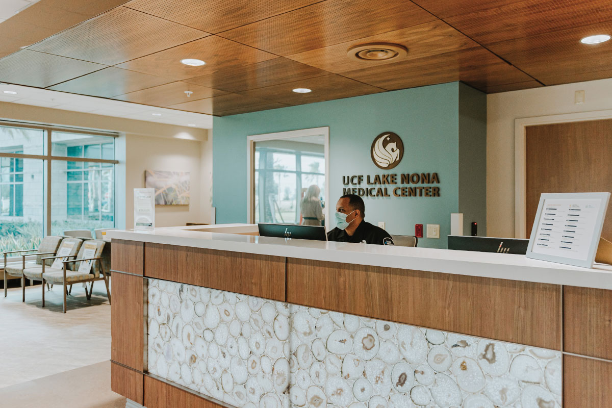 A security guard sits at the reception desk of the ER.