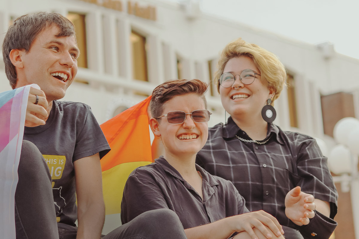 Three students laugh while holding various pride flags