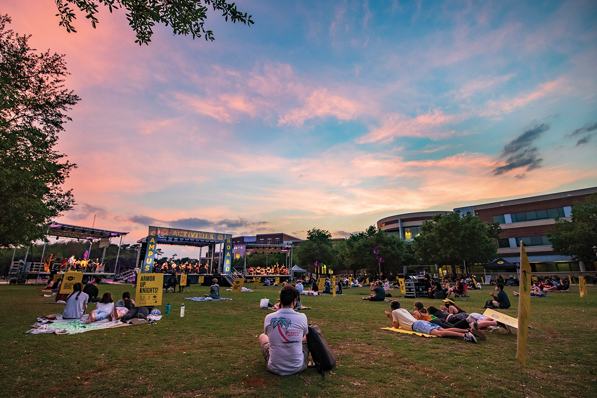 The sun sets as Knights sit on Memory Mall during a concert