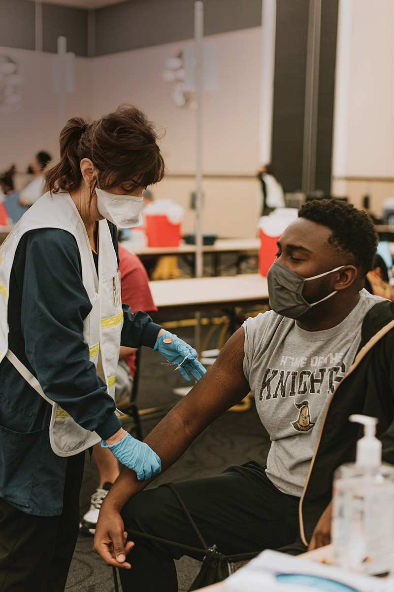 A student receives a COVID-19 vaccine from a UCF Student Health Services employee