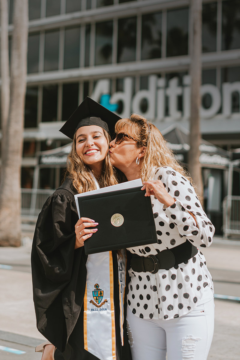 A Spring 2021 graduate poses for a photo with a family member in front of Addition Financial Arena.