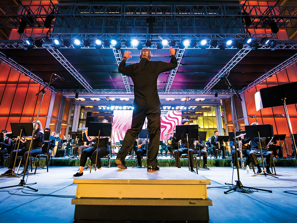 A man conducting a band on stage