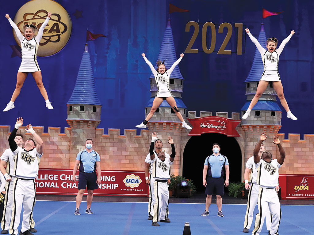 Cheerleading team during a performance, three flyers in the air as their spotters prepare to catch them