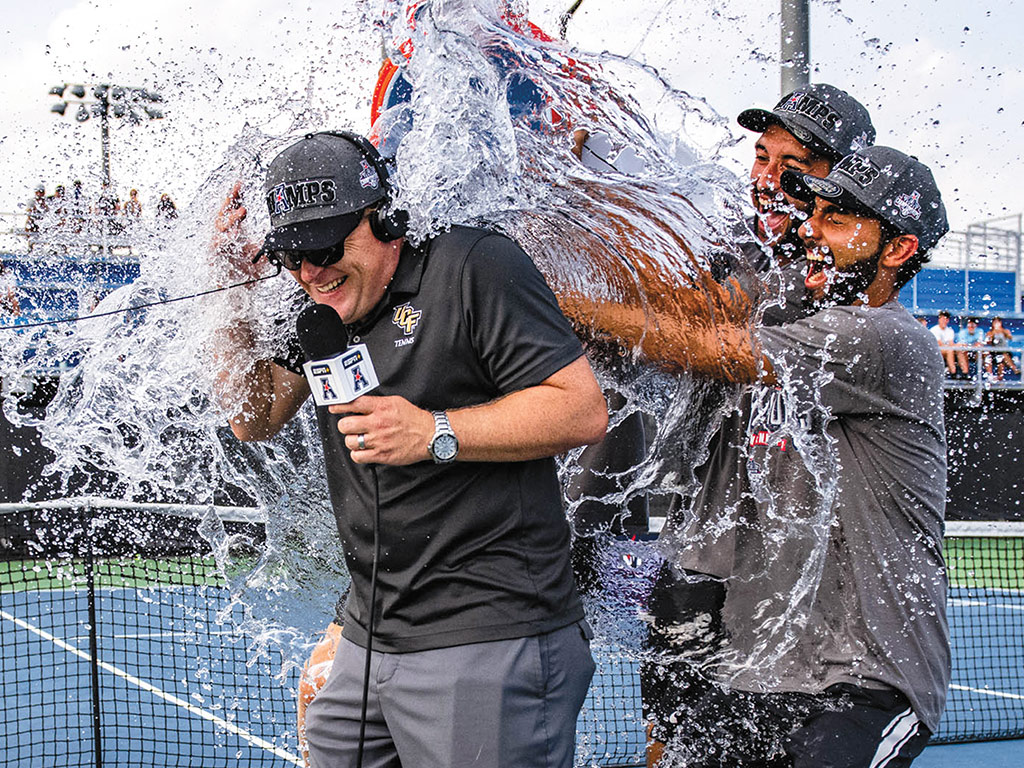UCF men's tennis head coach John Roddick gets water dumped on him by three athletes in celebration of a championship