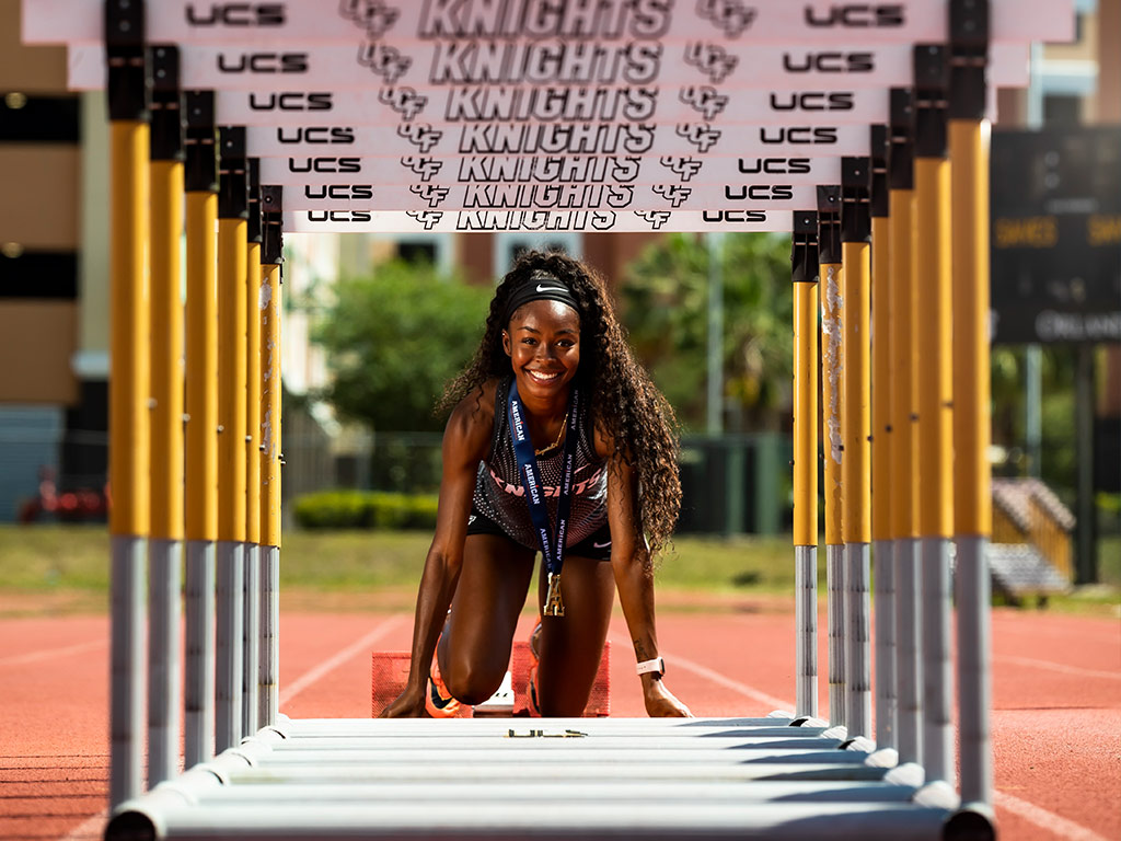Portrait of Rayniah Jones in the starting blocks, framed by a tunnel of hurdles lined up in front of her